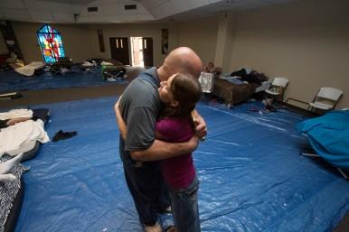 Shelter director, Allen Smith, hugs volunteer Christine Erwin at Woodcrest United Methodist Church in Lumberton, Texas. Photo by Kathleen Barry, UMNS